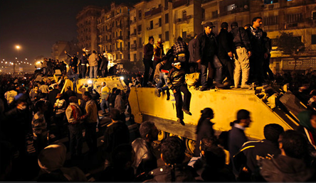 Protestors sit atop military vehicles